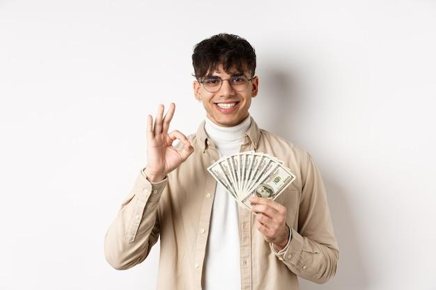 Красивый современный человек в очках показывает долларовые купюры и хорошо жест, зарабатывая деньги, стоя с наличными деньгами на белой стене.