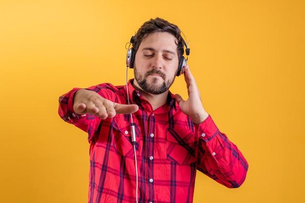 Handsome modern man listening music in headphones on yellow