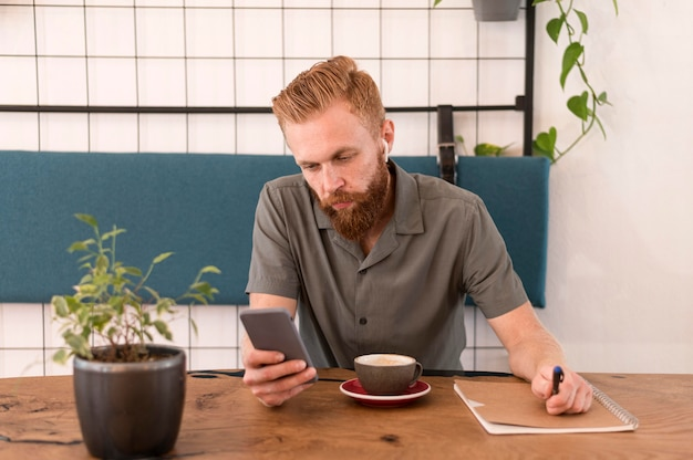 Bell'uomo moderno guardando il suo telefono