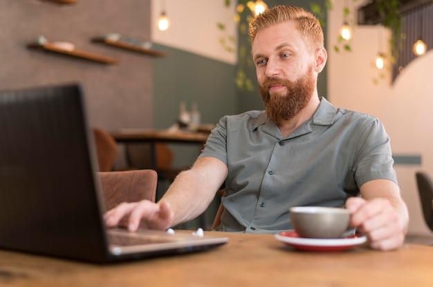 一杯のコーヒーの横で働くハンサムな現代人