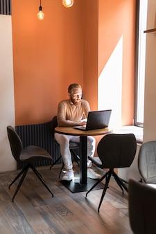 Bell'uomo moderno che lavora in ufficio