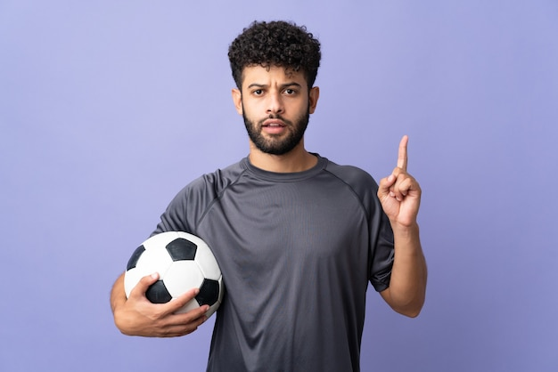Handsome moroccan young football player man over isolated on purple thinking an idea pointing the finger up