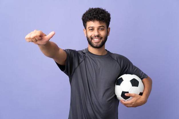 親指を立てるジェスチャーを与える紫色に孤立したハンサムなモロッコの若いサッカー選手の男 Premium写真