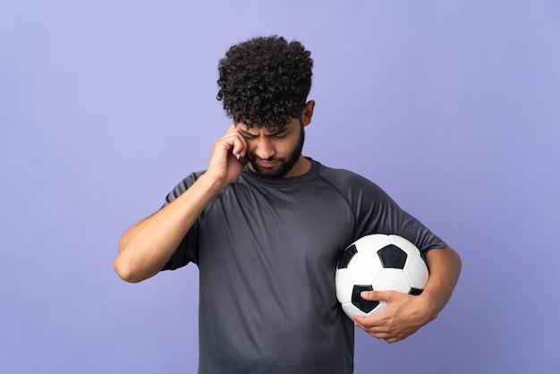 欲求不満と耳を覆う紫色の背景に孤立したハンサムなモロッコの若いサッカー選手の男