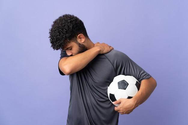 努力をしたために肩の痛みに苦しんでいる紫色の背景に孤立したハンサムなモロッコの若いサッカー選手の男