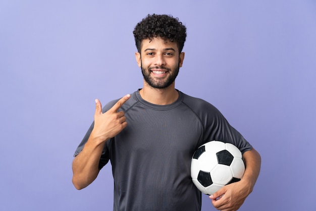 親指を立てるジェスチャーを与える紫色の壁に孤立したハンサムなモロッコの若いサッカー選手の男 Premium写真