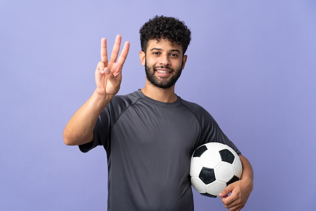 幸せで、指で3を数える紫色の壁に孤立したハンサムなモロッコの若いサッカー選手の男