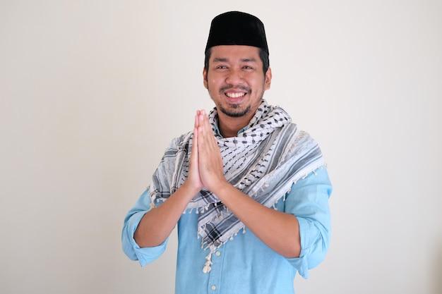 손으로 기도하는 제스처를 하는 동안 웃는 잘생긴 이슬람 아시아 남자
