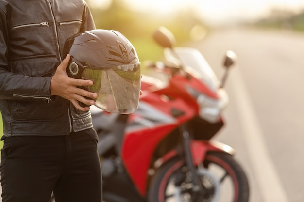 Handsome motorcyclist wear leather jacket, holding helmet on the road