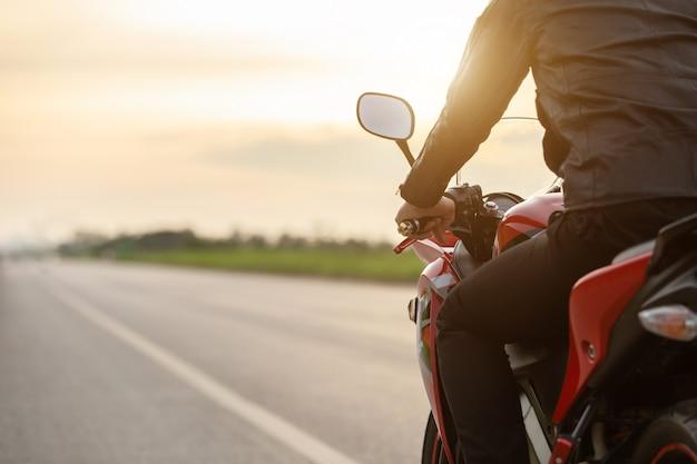 ハンサムなモーターサイクリストは道路でバイクの上に座って革のジャケットを着る