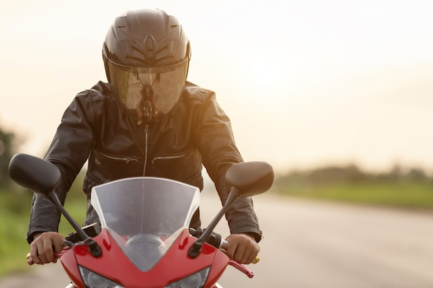 Handsome motorcyclist wearing leather jacket and holding helmet on the road