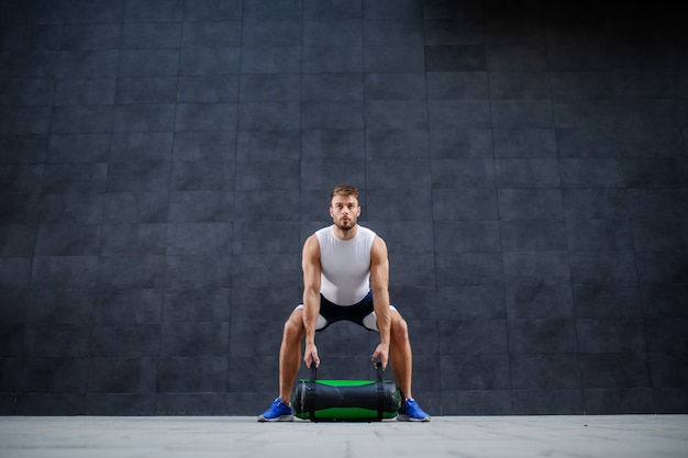 Handsome muscular bearded caucasian man in shorts and t-shirt lifting training bag while standing outdoor in front of gray wall.