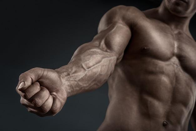 ハンサムな筋肉のボディービルダーは彼の拳と静脈、血管を示しています