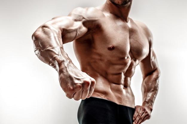 Handsome muscular bodybuilder demonstrates his fist and vein, blood vessels. studio shot on white background.