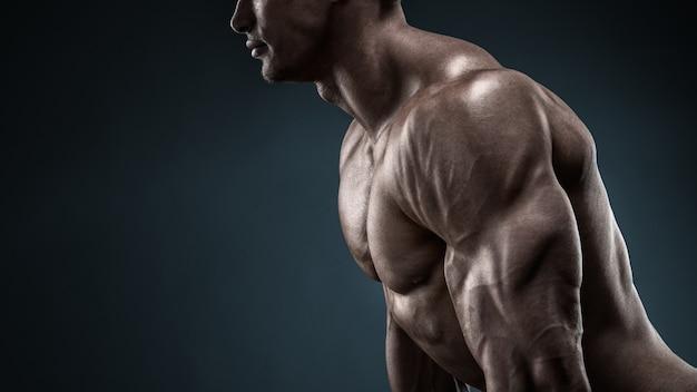 自信を持って楽しみにして、フィットネストレーニングの準備をしているハンサムな筋肉のボディービルダー。黒の背景で撮影したスタジオ。