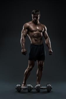 フィットネストレーニングの準備をしているハンサムな筋肉のボディービルダー。黒の背景で撮影したスタジオ。