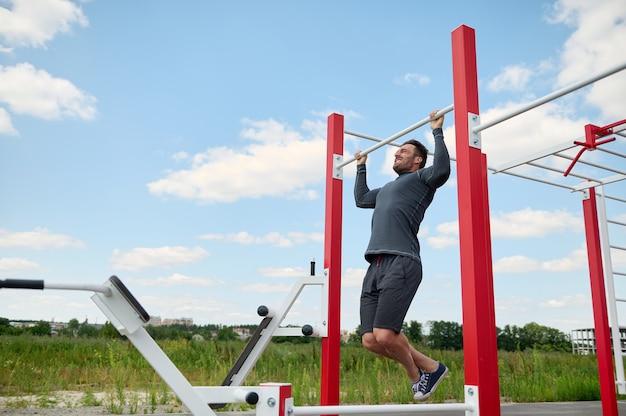 夏の運動場で屋外のクロスバーで働いているハンサムな筋肉の構築された成熟したヨーロッパの白人スポーツマン。健康的なアクティブなライフスタイル、屋外でのトレーニング、フィットネス、ボディービルの概念