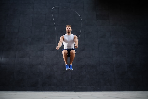 Handsome muscular caucasian man in shorts and t-shirt skipping rope in front of gray wall outdoors.