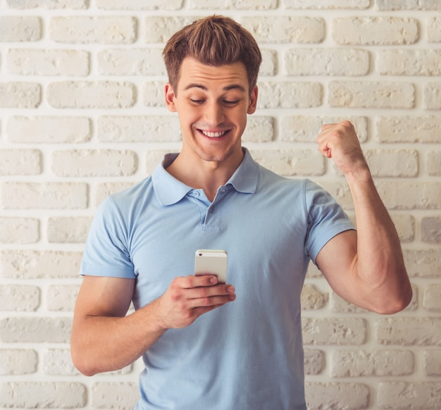 Handsome muscular guy in blue t-shirt is using smartphone