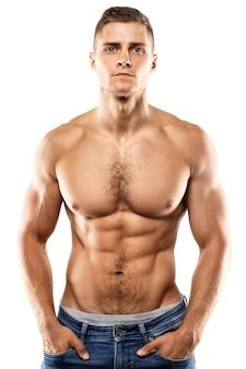 잘 생긴 근육 질의 남자는 흰 벽에 포즈
