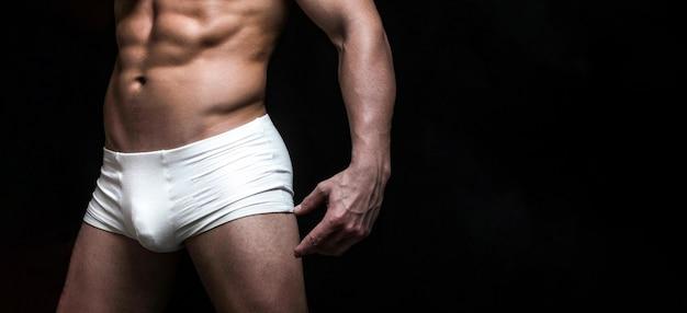 흰 속옷을 입은 잘생긴 근육질의 사나이. 남성 수영복, 반바지, 속옷, 개념. 흰색 섹시한 속옷에 남성 근육질의 몸. 흰색 반바지에 잘생긴 남자입니다. 공간을 복사합니다.
