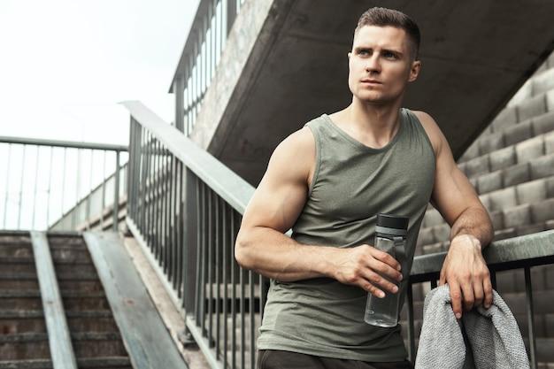 Красивый мускулистый мужчина после тренировки на улице города