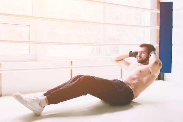 Handsome muscular man doing sit-ups on a wooden floor.