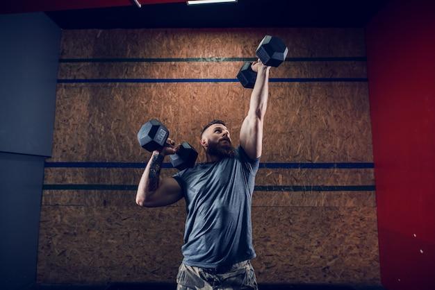 空気中のダンベルを持ち上げ、ジムで立ちながら見上げるtシャツでハンサムな筋肉男。夜のワークアウトのコンセプト。