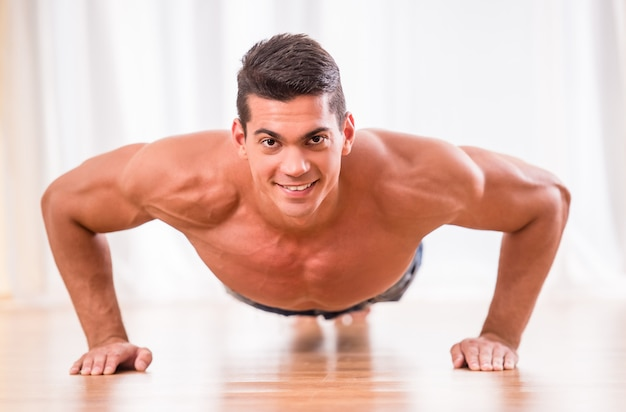 Handsome muscular man is doing push ups.