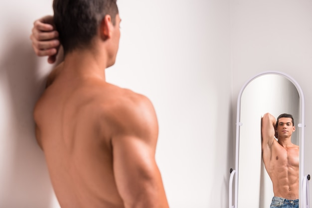 Handsome muscular man is looking at himself in the mirror.