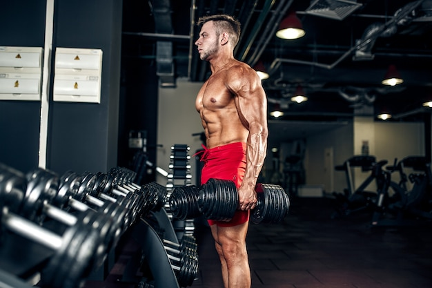 Handsome muscular man posing at a gym