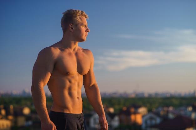 Красивый мускулистый мужчина позирует на фоне голубого неба. концепция здорового образа жизни.