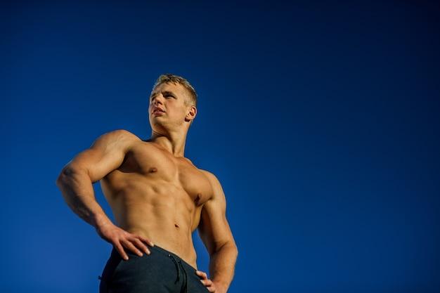 푸른 하늘 포즈 잘 생긴 근육 질의 남자