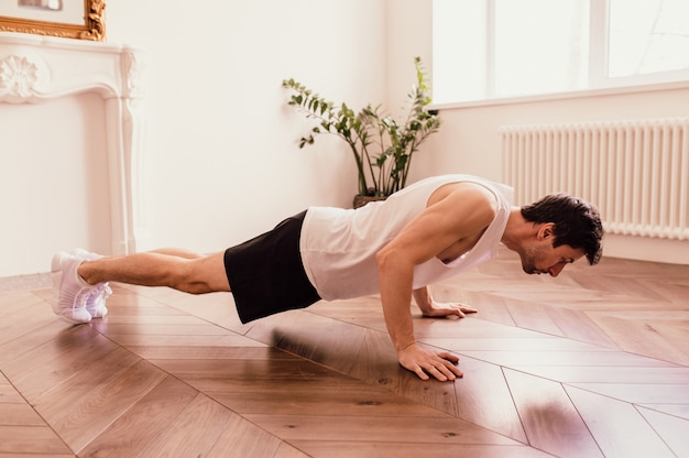 Handsome muscular man in a t-shirt and shorts doing functional exercises on floor at home
