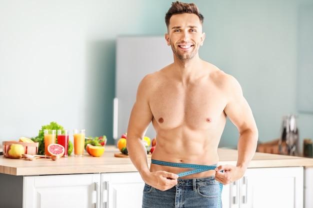 キッチンで巻尺を持つハンサムな筋肉質の男。減量の概念