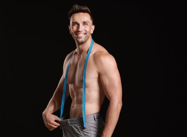 暗い背景に巻尺を持つハンサムな筋肉の男。減量の概念