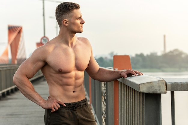 Handsome muscular man with naked torso during fitness workout on a bridge
