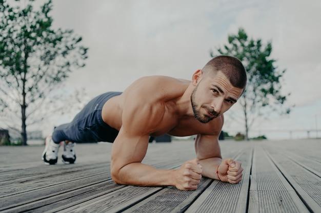 Красивый мускулистый мужчина с голым торсом на открытом воздухе делает фитнес-тренировку