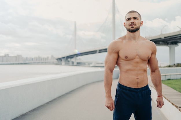 Handsome muscular man with naked torso outdoors doing fitness workout