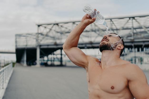 屋外でフィットネストレーニングをしている裸の胴体を持つハンサムな筋肉質の男