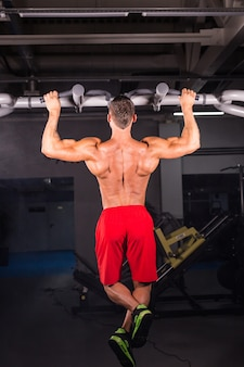 Handsome muscular man with perfect body doing pull ups in gym.