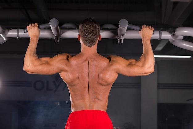 체육관에서 풀업을하는 완벽한 몸매를 가진 잘 생긴 근육질의 남자