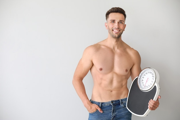 Красивый мускулистый мужчина с весами. концепция потери веса