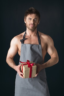 Handsome muscular naked man in an apron holding holiday gift box