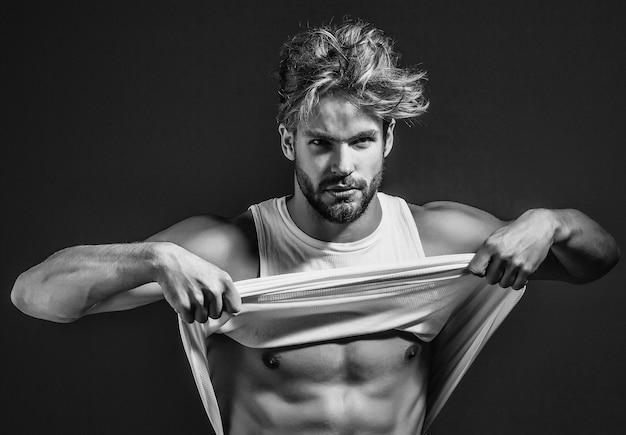 白いベストのハンサムな筋肉のセクシーな男は、裸の筋肉の胴体と胸を持っています。服を脱ぐ