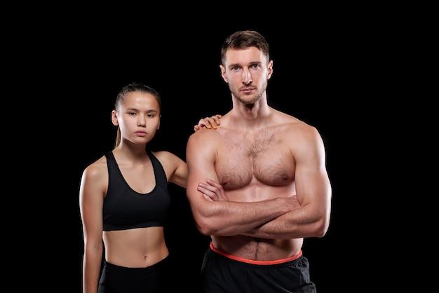 Красивый мускулистый парень без рубашки и его красивая девушка в спортивной одежде стоят рядом