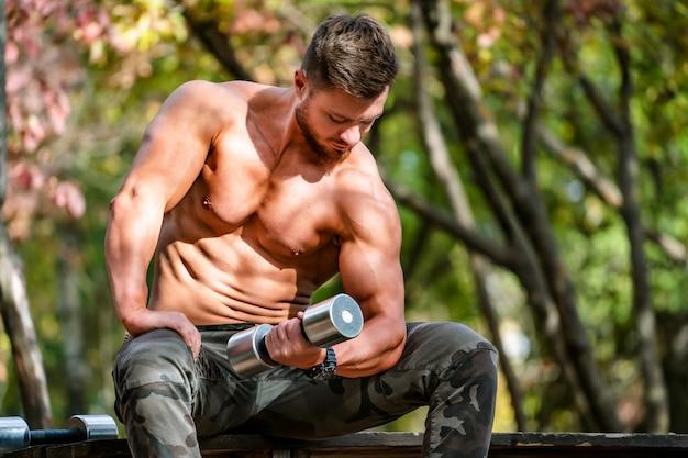 잘 생긴 근육 질의 벗은 덩어리 야외 야외 설정에서 남자. 건강한 몸을 보여줍니다. 반쯤 벗은 운동가. 공원 경치. dumbbel, 흐린 배경 작업.