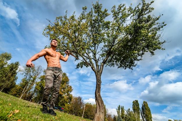 잘 생긴 근육 질의 벗은 덩어리 야외 야외 설정에서 남자. 건강한 몸을 보여줍니다. 반쯤 벗은 운동가. 공원 경치.