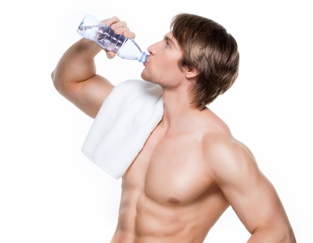 Handsome muscular shirtless sportsman drinks water