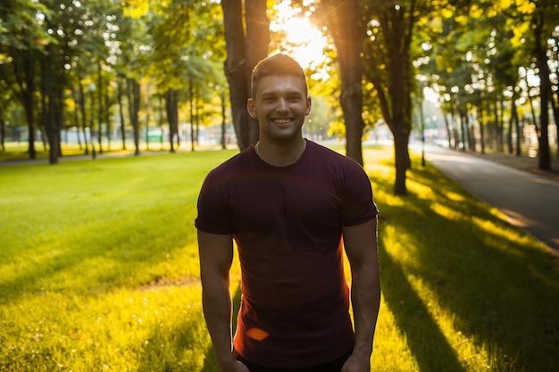 ハンサムな筋肉の笑顔の男の写真の肖像画。アクティブで自信のある人々のライフスタイル。公園で散歩